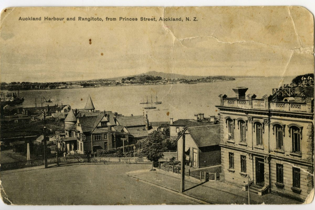 Postcard of 'Auckland Harbour and Rangitoto from Princes Street, Auckland, NZ.' showing Admiralty House in the centre as well as the old Auckland Museum building and caretakers house on Princes Street (right foreground). 2018.145.1